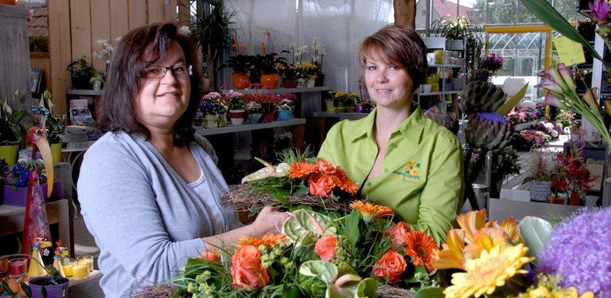 Eine Mitarbeiterin überreicht gebundenen Blumenstrauß