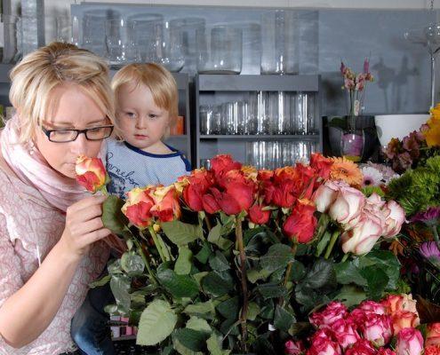 Kunden mit Kind auf dem Arm schnuppert an Rose