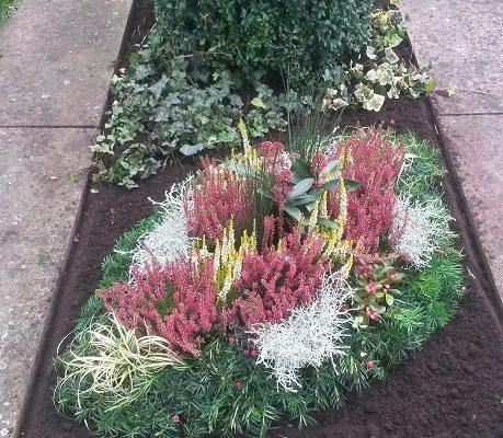 Schöne Herbstbepflanzung eines Grabes