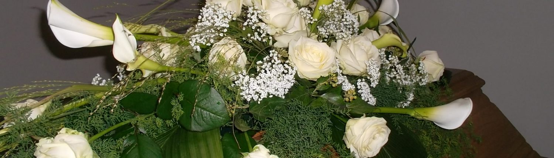 Sarggebinde mit Rosen und Calla Pflanzen