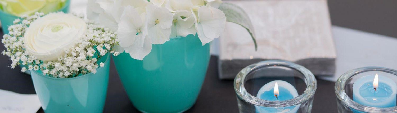 Tischdekoration in blau-grün mit Blüten, Läufer und Kerzen